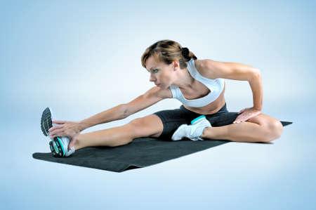 Sport fitness woman doing exercise on a black gym mat on a gray background. Studio shooting Lizenzfreie Bilder