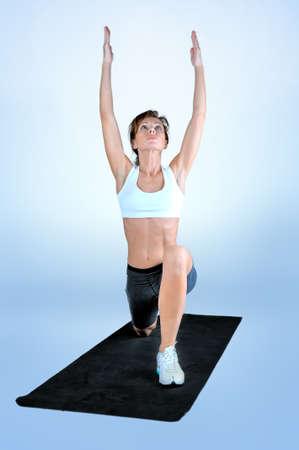 Sport Fitness Frau auf einem schwarzen Gymnastikmatte auf einem grauen Hintergrund, der Übung tut. Studioschießen