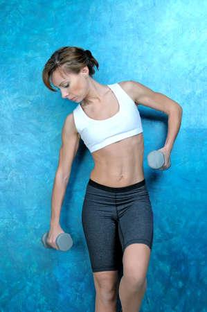 Sport Frau in der Kleidung für Fitness und türkis Sneakers steht in der Nähe einer blauen Wand und hält graue Hanteln in Händen. Studio schießen Lizenzfreie Bilder