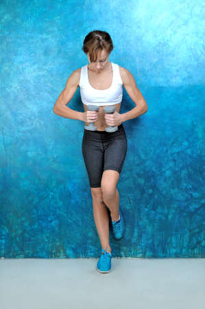 Sport woman in wear for fitness and turquoise sneakers stands near a blue wall and holds gray dumbbells in hands. Studio shoot. Lizenzfreie Bilder