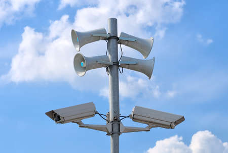 CCTV security cameras and loudspeakers against blue sky with white clouds