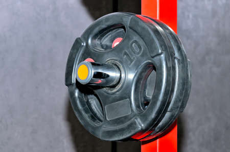 Black barbell plates with an inscription of 10 kg on a red metal rack on a gray background. Close up