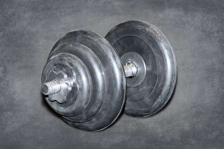 Large black dumbbell for weight lifting on a dark background