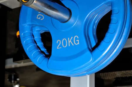 Blue barbell plates with an inscription of 20 kg on a metal rack on a dark background in a sports, fitness club. Close up