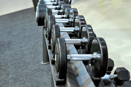 Row of black metal dumbbells on rack in the gym, sport club. Weight training equipment.