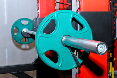 Barbell with green barbell plates with an inscription of 10 kg on a metal rack on a sports, fitness club