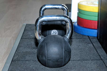Black metal weight with an inscription of 20 kg and colour barbell plates on a floor in sports, fitness club.