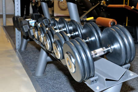 Row of metal black dumbbells on rack in the gym, sport club. Weight training equipment.