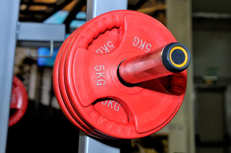 Red barbell plates with an inscription of 5 kg on a metal rack on a dark background in a sports, fitness club. Close up Lizenzfreie Bilder