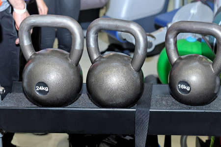 Gray metal weights with an inscription of 24 and 16 kg on a metal rack on a dark background in a sports, fitness club Lizenzfreie Bilder