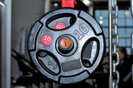 Black barbell plates with an inscription of 10 kg on a red metal rack on a dark background in a sports, fitness club. Close up Lizenzfreie Bilder