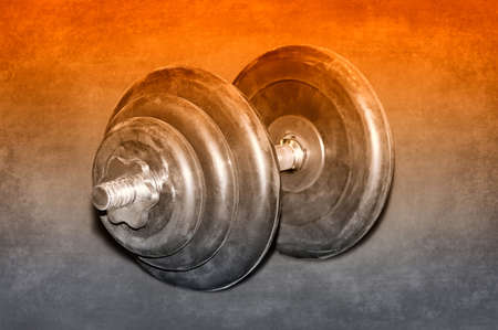 Large black dumbbell for weight lifting on a dark background. Selective toned image