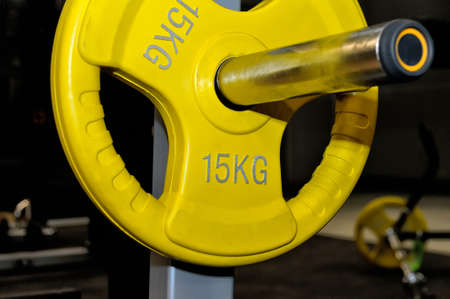 fifteen: Yellow barbell plate with an inscription of 15 kg on a metal rack on a dark background in a sports, fitness club. Close up Stock Photo