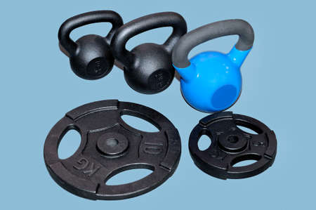 Black and blue metal weights and black metal barbell plates isolated on a grey background