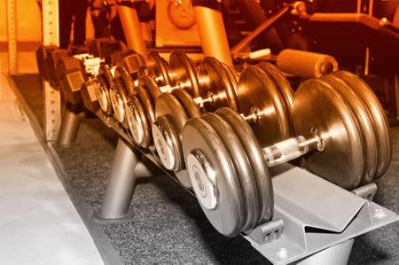 Row of black metal dumbbells on rack in the gym, sport club. Weight training equipment.Selective toned image Lizenzfreie Bilder