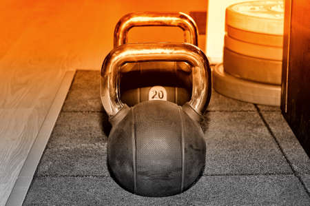 Black metal weight with an inscription of 20 kg and colour on a red metal rack on a dark background in a sports, fitness club. Selective toned