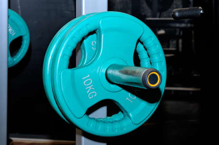 Green barbell plates with an inscription of 10 kg on a metal rack on a dark background in a sports, fitness club. Close up