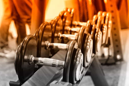 Row of black metal dumbbells on rack in the gym, sport club. Weight training equipment.Selective toning image