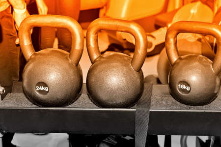 Grey metal weights with an inscription of 24 and 16 kg on a metal rack on a dark background in a sports, fitness club. Selective toned Lizenzfreie Bilder