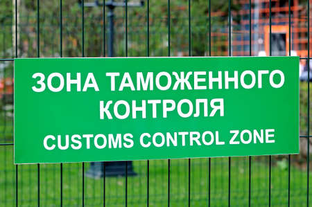 Green sign with the inscription in Russian and English: Customs control zone on the fence of metal rods. Side view Lizenzfreie Bilder