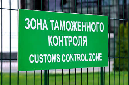 Green sign with the inscription in Russian and English: Customs control zone on the fence of metal rods. Side view. Shallow depth of field