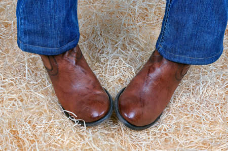 Pair of legs in traditional vintage brown cowboy boots and blue classic jeans posing on straw