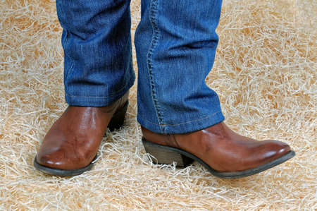 Paar Beine in traditionellen Vintage braunen Cowboystiefel und blauen klassischen Jeans posieren auf Stroh