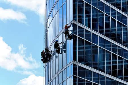 Los escaladores industriales lavan las ventanas delanteras de un rascacielos moderno Foto de archivo - 84266366