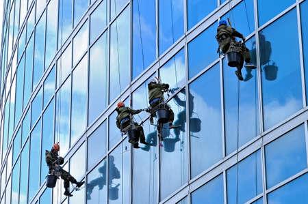 Industrielle Bergsteiger waschen die Frontscheibe eines modernen Wolkenkratzers Standard-Bild - 84203410