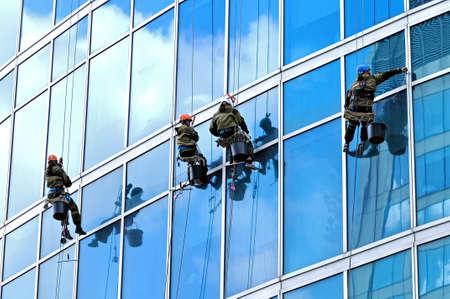Los escaladores industriales lavan las ventanas delanteras de un rascacielos moderno