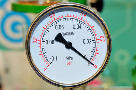 Pressure gauge on a blurry industrial background.