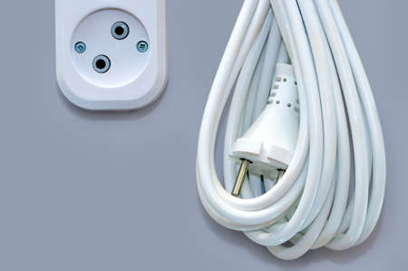 wired: White electric socket and electric wire extension with a plug isolated on a gray background Stock Photo