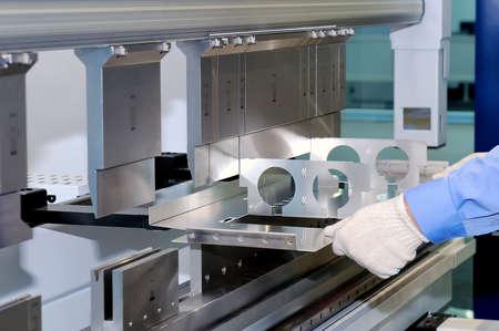 Worker bends a metal plate on the industrial machine. Lizenzfreie Bilder