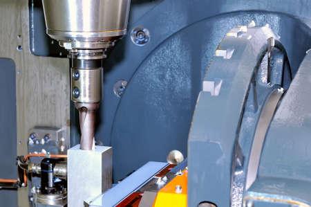 Industrial metalworking machine tool processes a metal rectangular workpiece Lizenzfreie Bilder