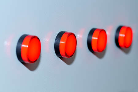 Red industrial switch buttons on a gray background. Shallow depth of field Lizenzfreie Bilder