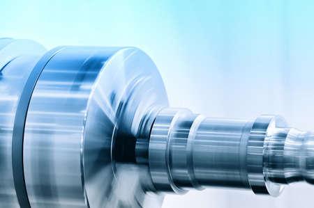 Rotating spindle of turning lathe and metal detail. Blue toning. Lizenzfreie Bilder