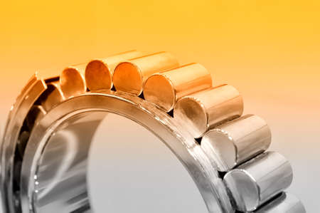 Industrial roller bearing on a light background. Red toning. Shallow depth of field, selective focus Stock Photo