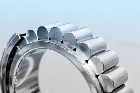 Industrial roller bearing on a light background. Blue toning. Shallow depth of field, selective focus
