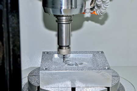 Machining of a metal part on an industrial milling machine. On a surface of a detail there are particles of metal and shaving