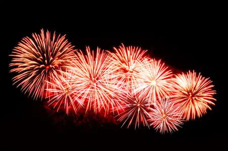 Red-white fireworks display on dark sky background. Lizenzfreie Bilder