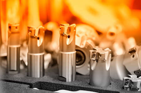 Set of steel milling cutters with cutting inserts. Red toning. Shallow depth of field, selective focus