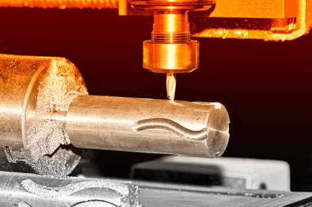 Spindle with a metal detail and a mill of the turning milling lathe machine. Small scratches and particles on the machine surface. Red toning. Shallow depth of field, selective focus