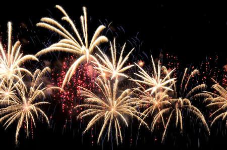 Erstaunliche weiße Feuerwerk und Streuung von roten und blauen Funken auf dunklem Hintergrund