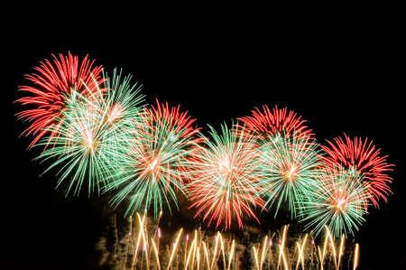 Amazing red and green fireworks on dark background. Lizenzfreie Bilder