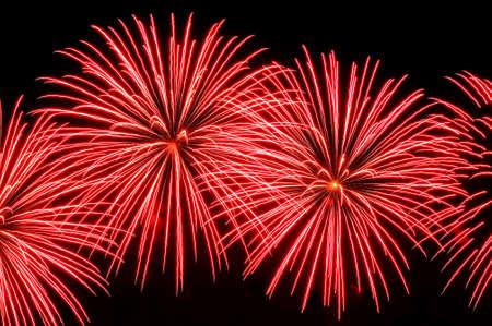 Flashes of fireworks of red color against the black sky Lizenzfreie Bilder