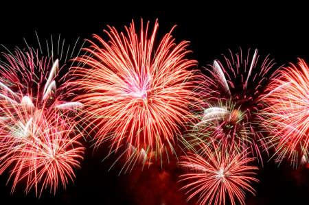 Flashes of fireworks of red color against the black sky.
