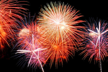 Red, white and pink fireworks display on dark sky background.