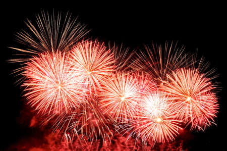 Flashes of fireworks of red, gold and white color against the black sky Lizenzfreie Bilder