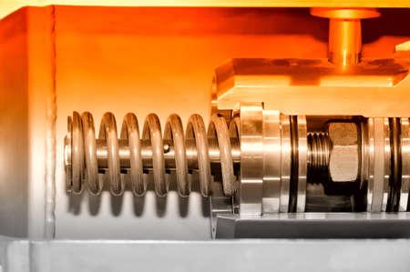 Part of the industrial mechanism with a metal spring. Red toning. Lizenzfreie Bilder