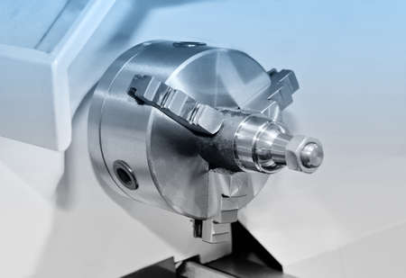 Spindle and a clamping mechanism for turning lathe. Blue toning. Shallow depth of field, selective focus Lizenzfreie Bilder